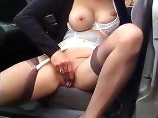 Super MILF woman rubs her pierced pussy in the car